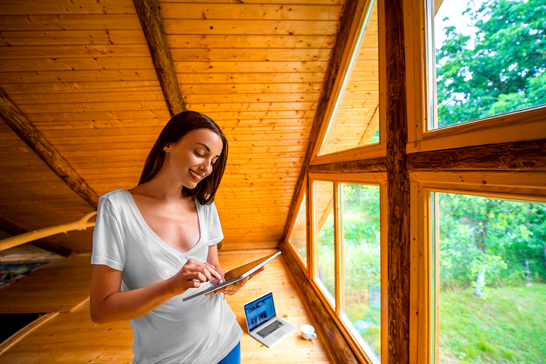 Woman in a log cabin house using a tablet to view her home inspection report online